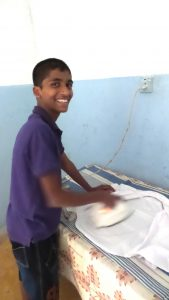 Ironing school uniform. The boys are encouraged to be self sufficient .